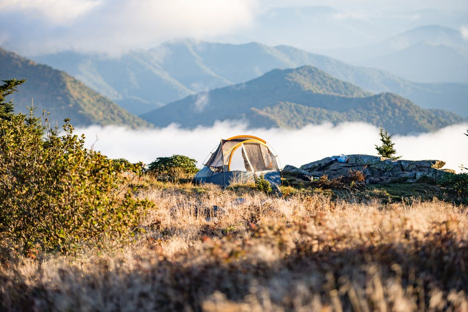 Teal and Yellow Dome Tent on Peach Leveled With Clouds Near Mountain Under Daytime