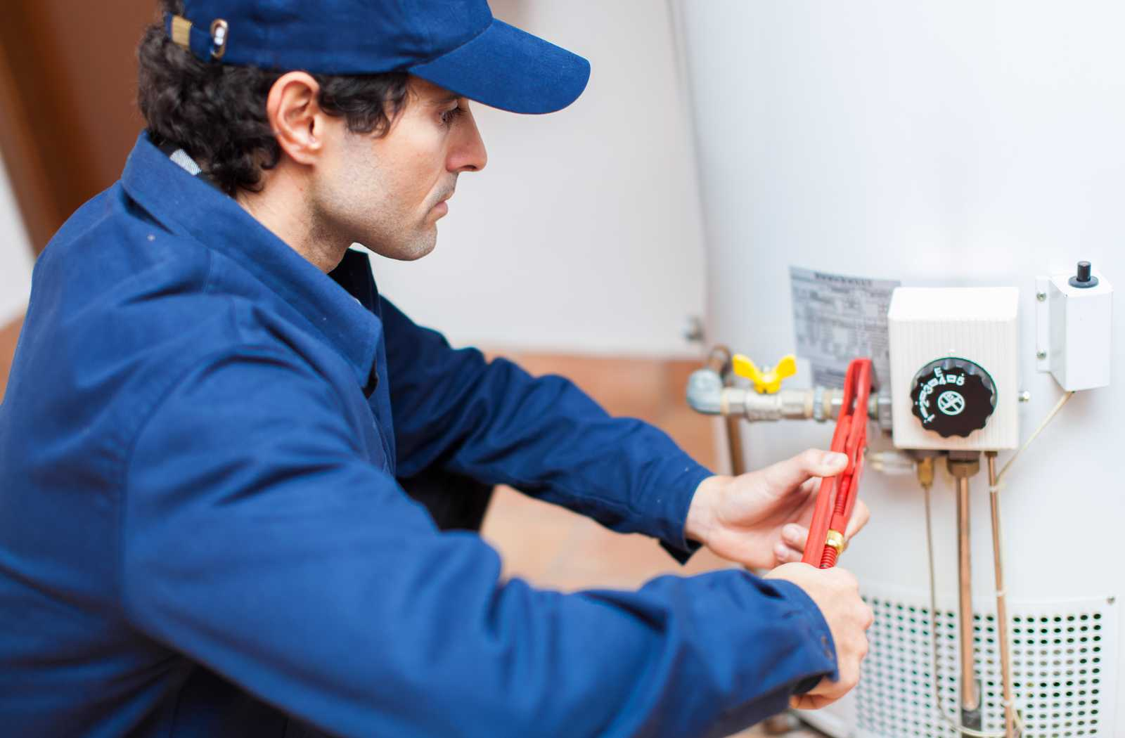 plumber in blue overalls working on white water heater