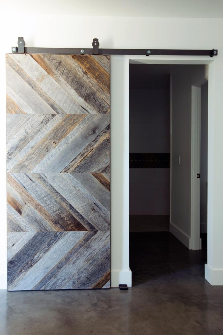 A hallway entrance with a barn door that has a unique chevron pattern with different colors of wood
