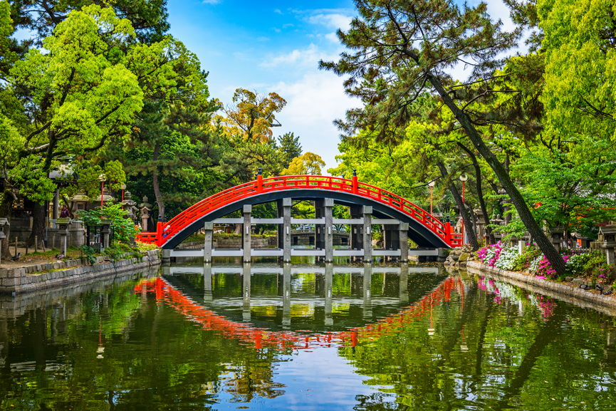 6 Best Places to Visit in Asia in 2020 featured by top travel blog, The Common Traveler: image of red footbridge over river in Osaka, Japan