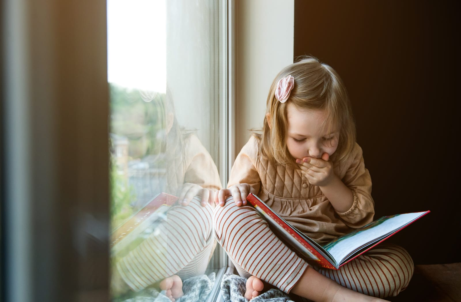 A young child reads a book in a well-lit room during the daytime to avoid affecting her sleep at night