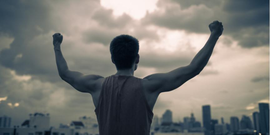man-raises-arms-in-triumph-over-city