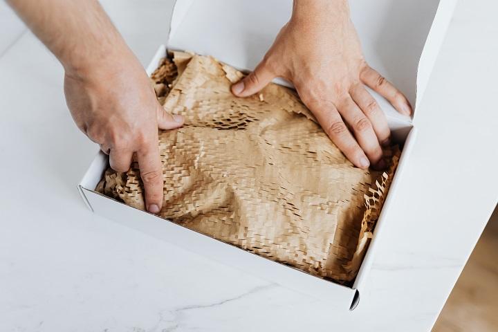 plataformas para e-commerces pequenos foto de mãos arrumando o produto dentro da embalagem