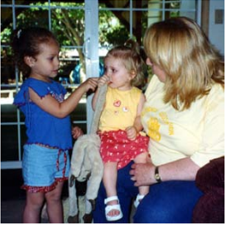 A caretaker holding a child, a child who was formerly crying, while antoher child talks to her