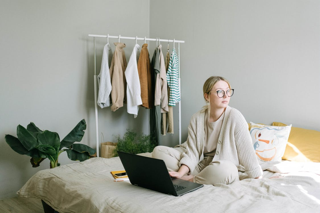 Woman in White Sweater Sitting on Bed