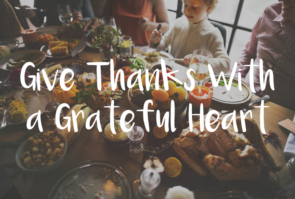 a Thanksgiving dinner laden table with the words Give Thanks with a Grateful Heart over it.