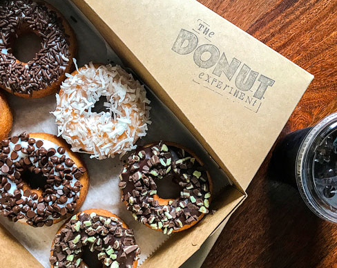 box of glazed donuts with chocolate toppings