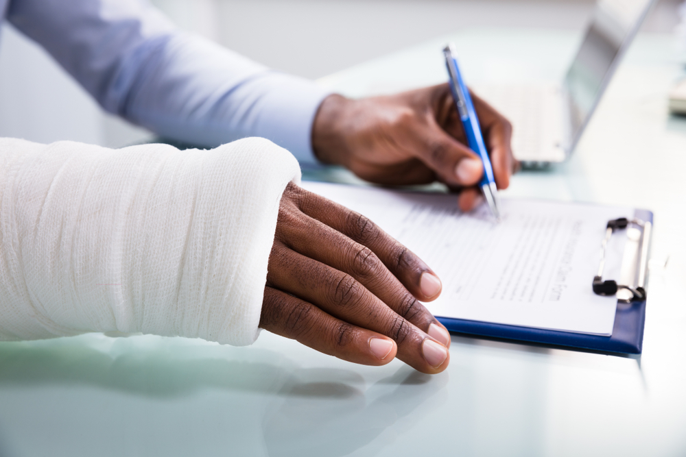 A man with and injured hand attempts to fill out paperwork on a cllipboard
