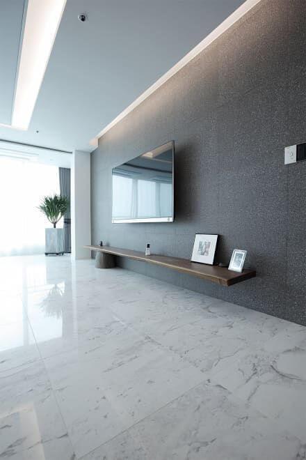 Sala com piso porcelanato imitando mármore, paredes cinza com TV e prateleira amadeira e teto claro
