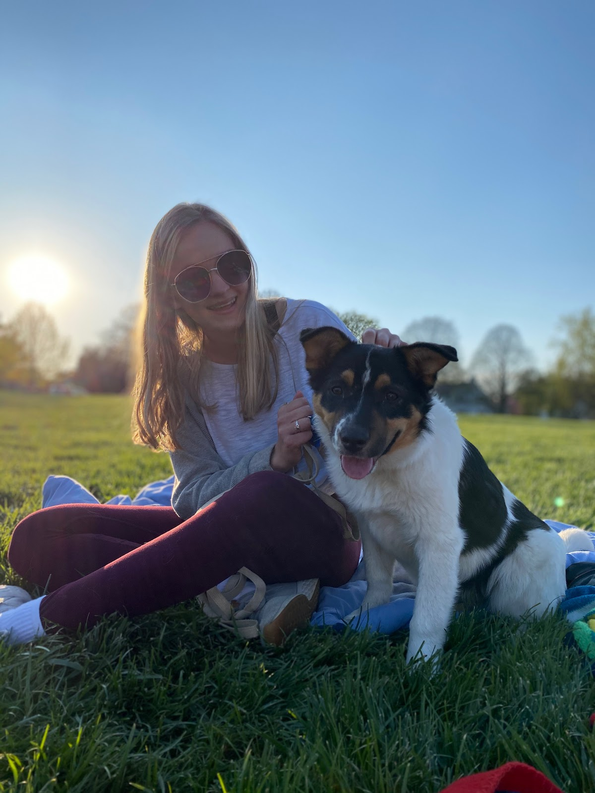 Evie McArthur sits with her puppy Lila in a grassy park.