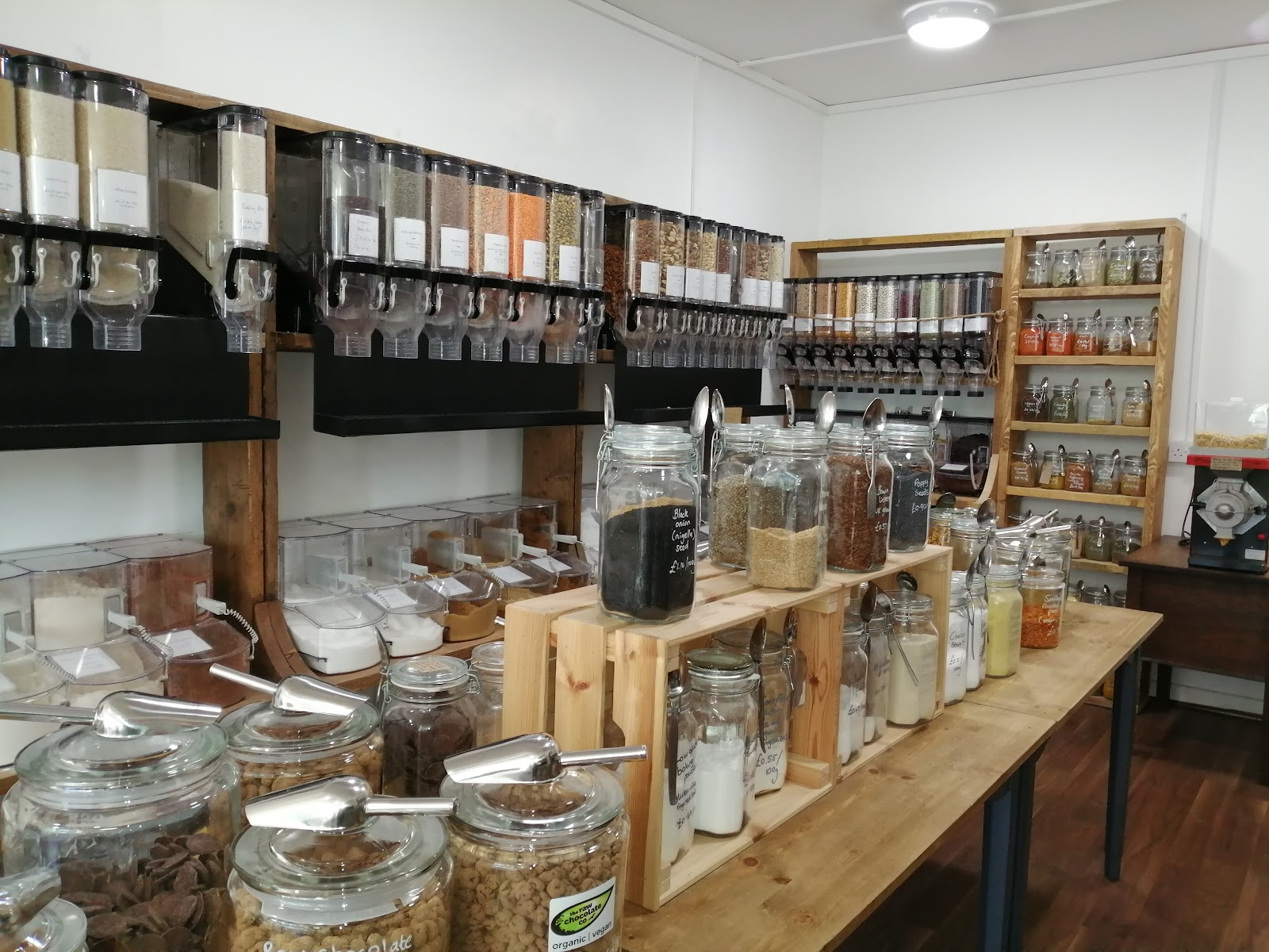 Inside Unwrapped. Containers filled with store cupboard essentials like flour, sugar, dried pulses and much more; a peanut butter dispenser; a wonderful range of chocolate and sweet treats as well as a selection of herbs, spices and snacks.
