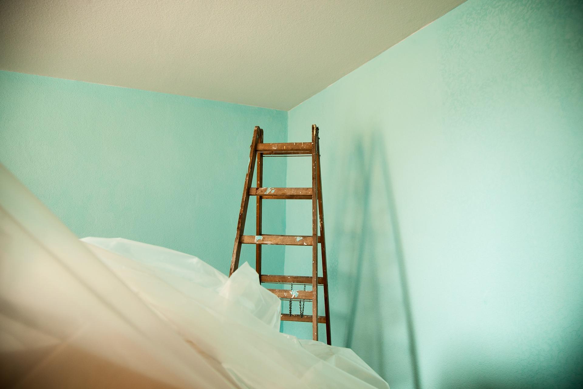 ambiente com escada de madeira dobrável e móveis cobertos com plástico