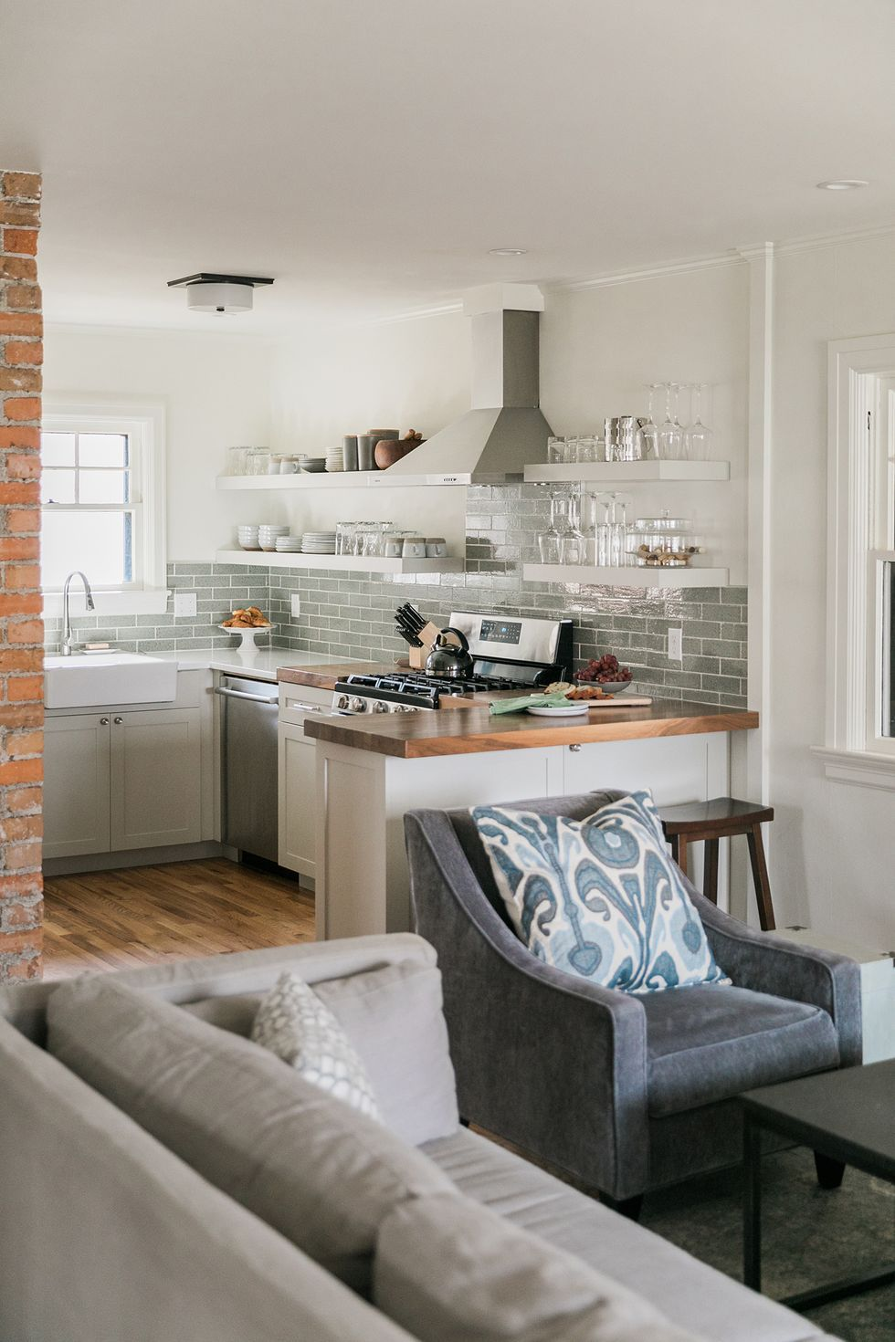small kitchen with white shaker cabinets and glossy gray subway tile backsplash. floating shelves house dishware and a wooden butcher block countertop is adjacent to a farmhouse sink