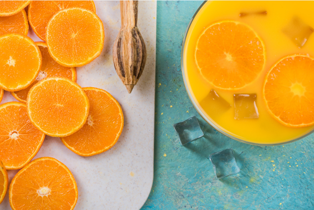 Orange slices sitting next to a glass of juice