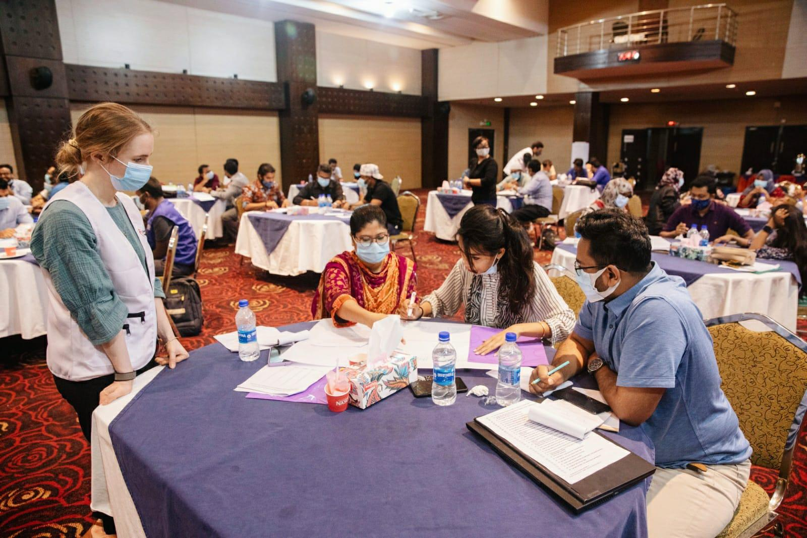 A group of clinical leaders and healthcare workers sitting at tables at a leadership & governance conference