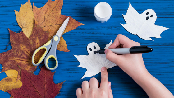 creating fall crafts with leaves, scissors, and paper ghost