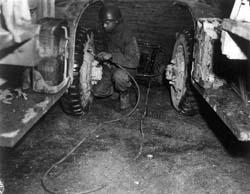 A truck driver fills a tire with air along the Red Ball Express highway during World War II. Photo courtesy Army Transportation Museum.
