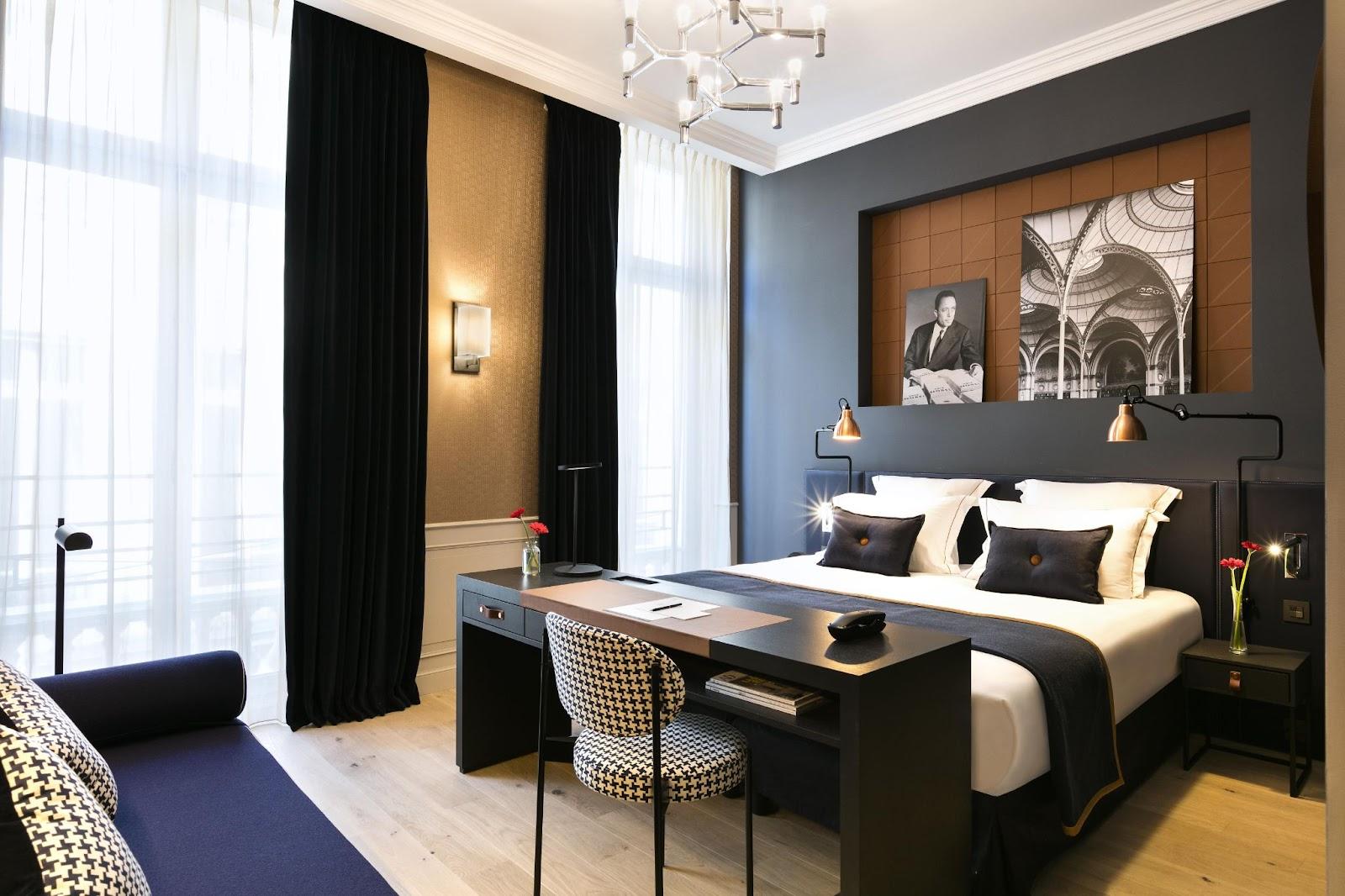 Chambre avec lit, bureau, canapé et grandes fenêtres
