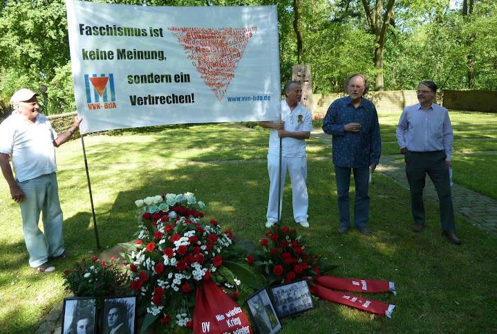 Gedenkende mit Kranz, Blumen, Bildern und Plakat: «Faschismus ist keine Meinung, sondern ein Verbrechen! VVN-BdA».