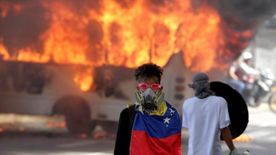 Opositores venezolanos prendieron fuego a varios autobuses y establecieron barricadas en una autopista en Caracas, 24 de abril de 2017.