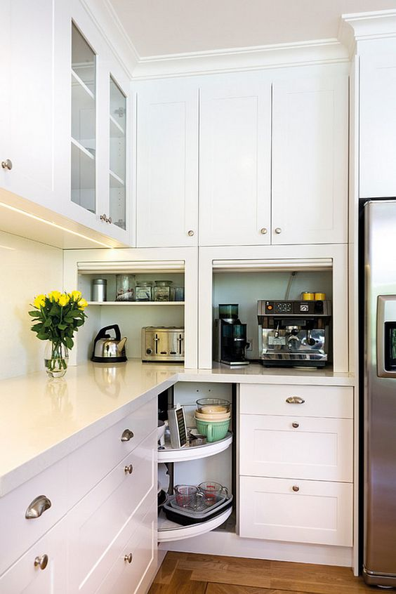 white kitchen with lazy susan in the corner cabinet. appliances garages are also used on the countertop to hide away kitchen utensils and tools