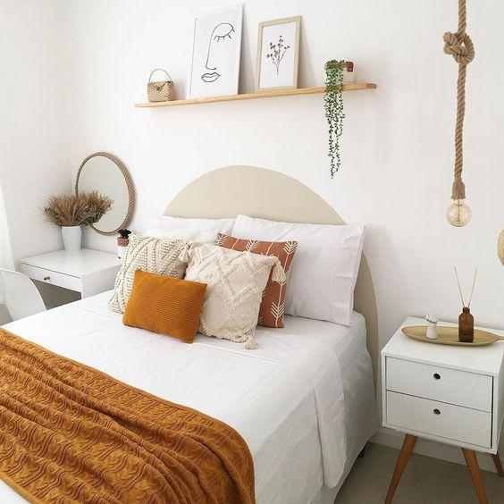 Quarto estilo rústico onde a cabeceira da cama foi substituído por pintura orgânica e quadros decorativos.