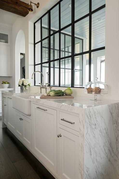naturally lit kitchen with white shaker cabinets, chrome hardware and white marble waterfall countertop