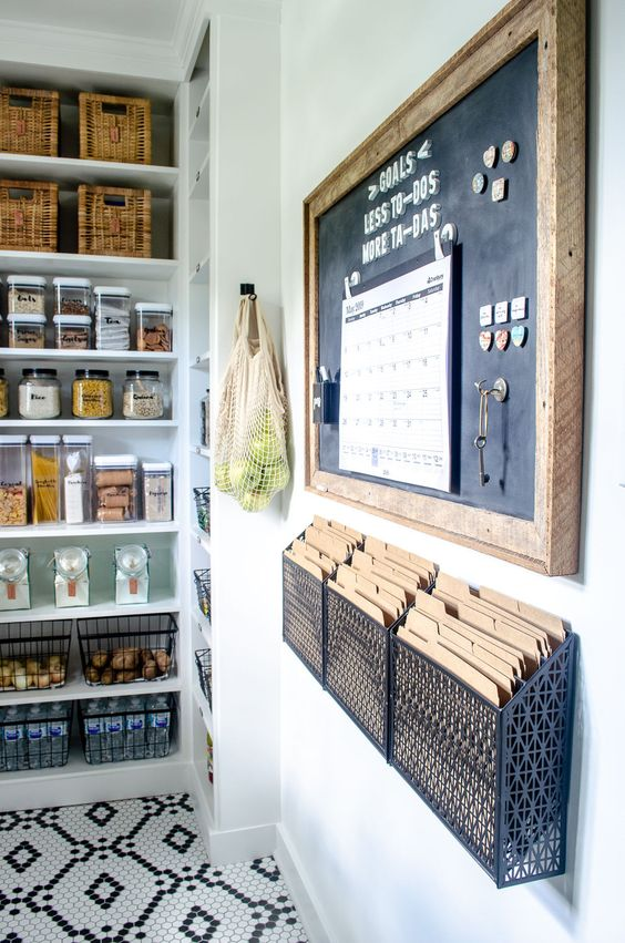 large walk in modern pantry idea with chalkboard and family command center on the walls, black and white tiled floors and glass jar containers