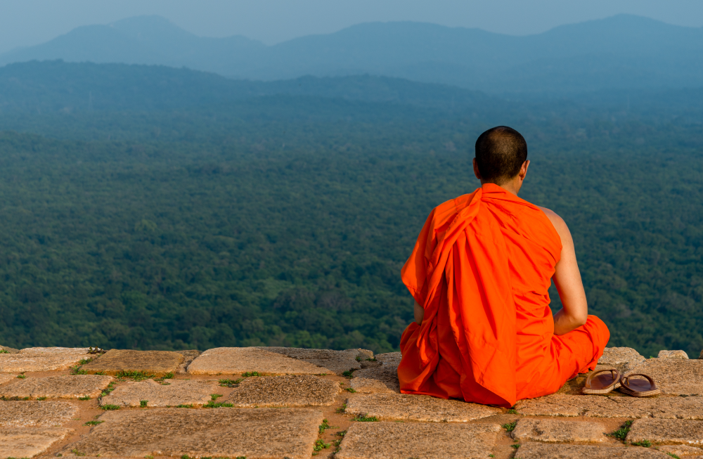https://blogs.holidaybazaar.com/wp-content/uploads/2019/08/budhist-monk-meditating-at-Lions-Rock-summit-Sigiriya-Sri-lanka.png