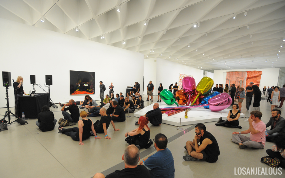 Museum-goers sit on the floor of the Broad to listen to a performer