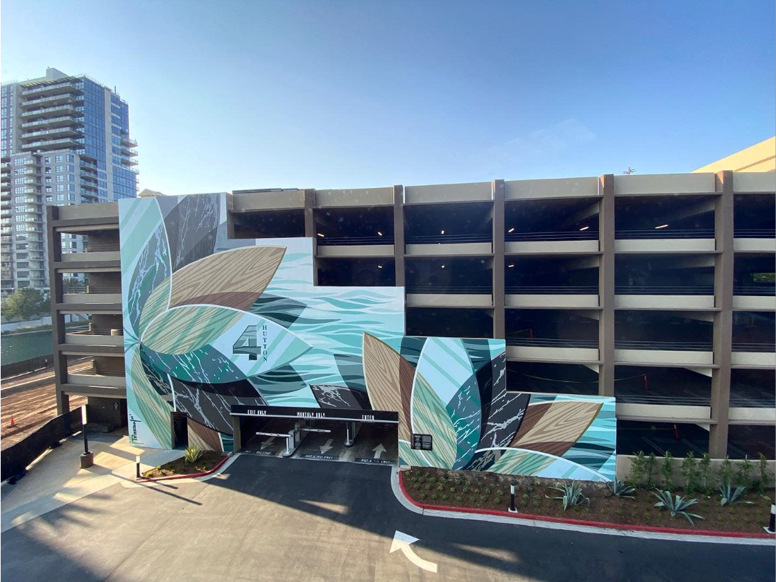 A mural painted on the side of a parking garage, the solid wall it's painted on steps down on each floor of the 5-story structure. The art is abstract, the subject is lotus flowers, the tones are neutral blues, with some greens and browns. On the far left, the tallest part of the solid wall, is a lotus flower with its base along the height of the wall. On the central petal is a darker blue 4 for the address of the garage. There is another flower on the lower left side, the lowest part of the wall, with its base beneath the ground.