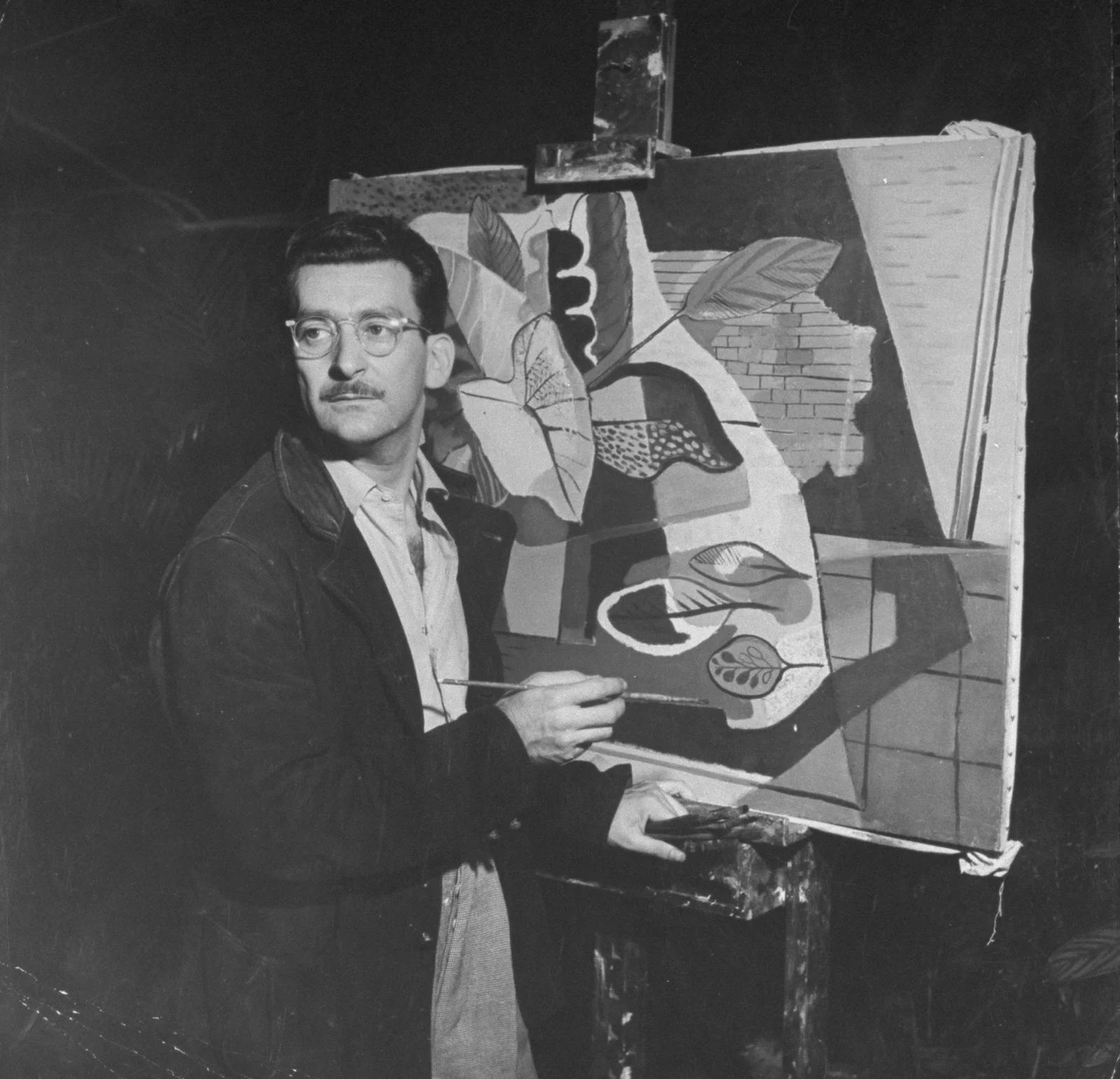 Fotografia de Burle Marx pintando uma tela que está apoiada em um cavalete. Em sua mão, há um pincel.