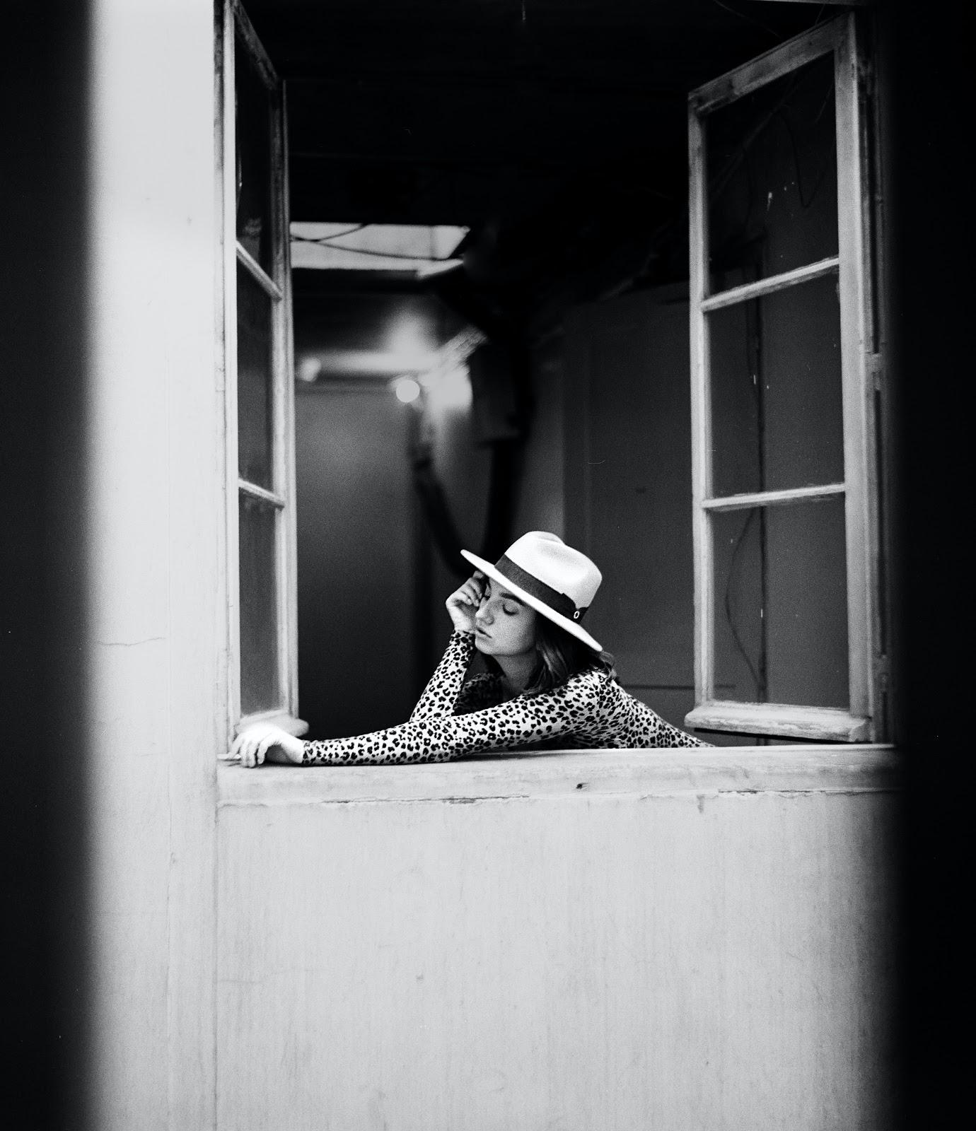 a girl in a white hat outside the window