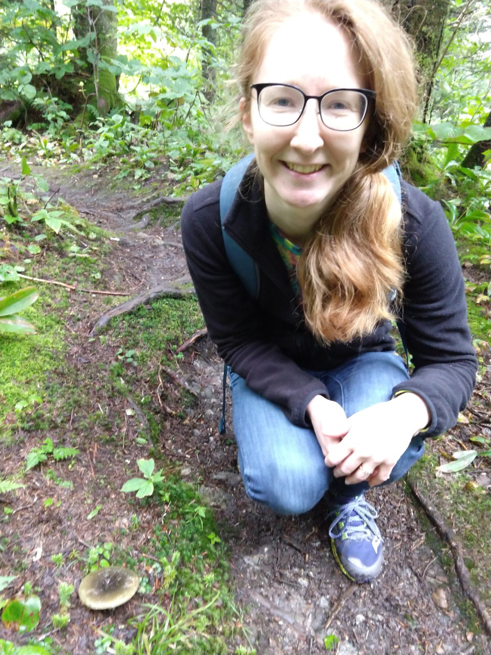 A person with glasses and a beard is crouching in the forest and smiling