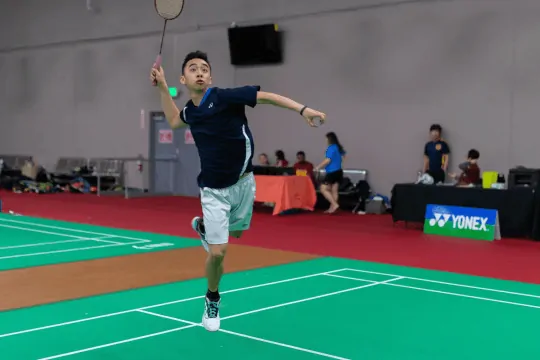 Justin Ma has his eyes on the shuttlecock, both feet off the court, and is in mid-air with his badminton racket ready to slam a badminton smash shot.  His face is full of concentration.