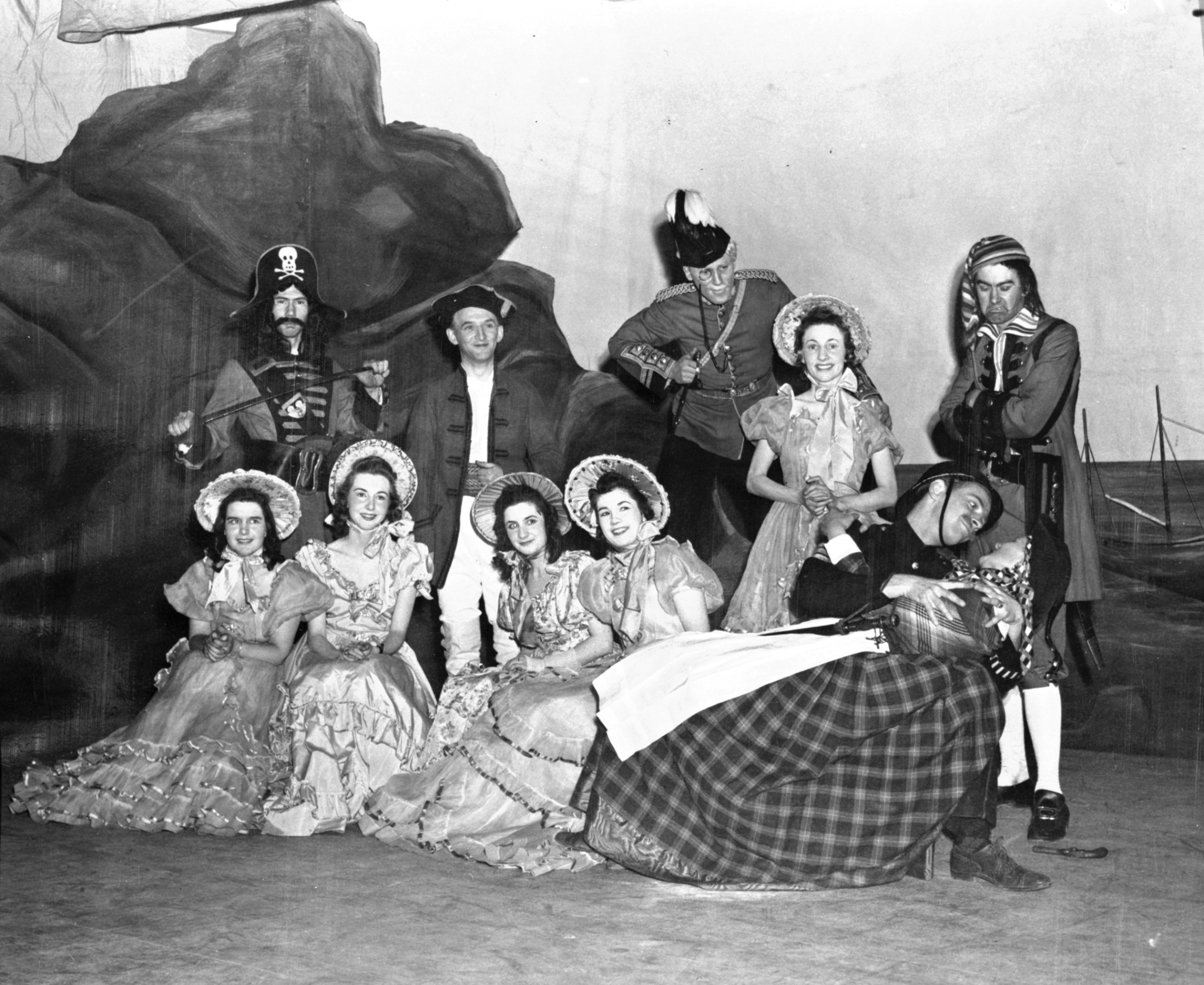 Black and white photo. Two rows of performers pose for the camera on stage. A rock and ship's masts are painted behind them. The men wear military uniforms and the women wear long frilly dresses with bonnets.