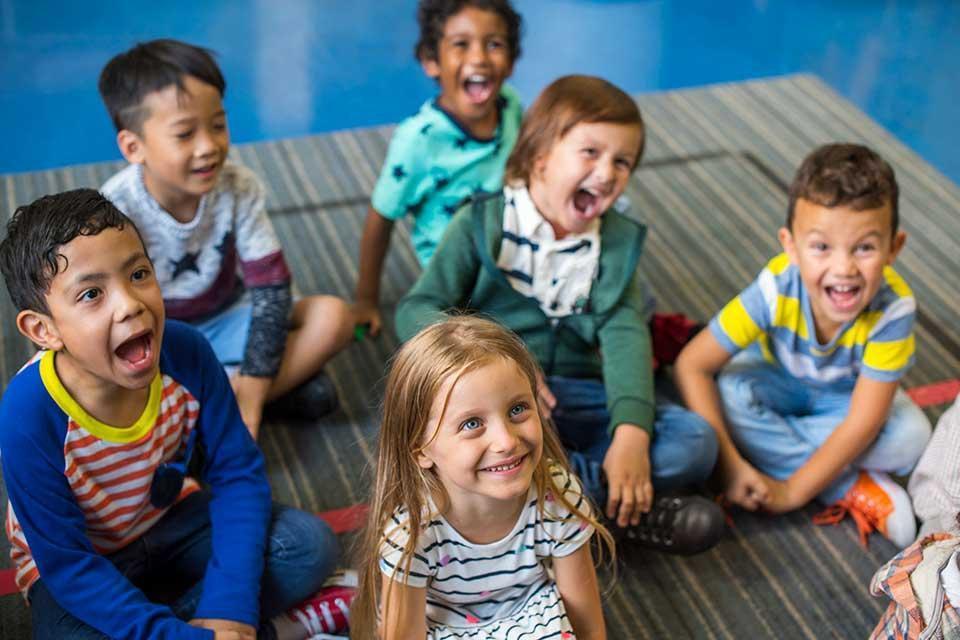 Grupo de pessoas sentadas em volta de uma criançaDescrição gerada automaticamente com confiança média