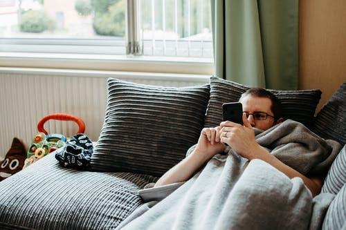 Photo of Man Lying on Gray Sofa While Using Smartphone