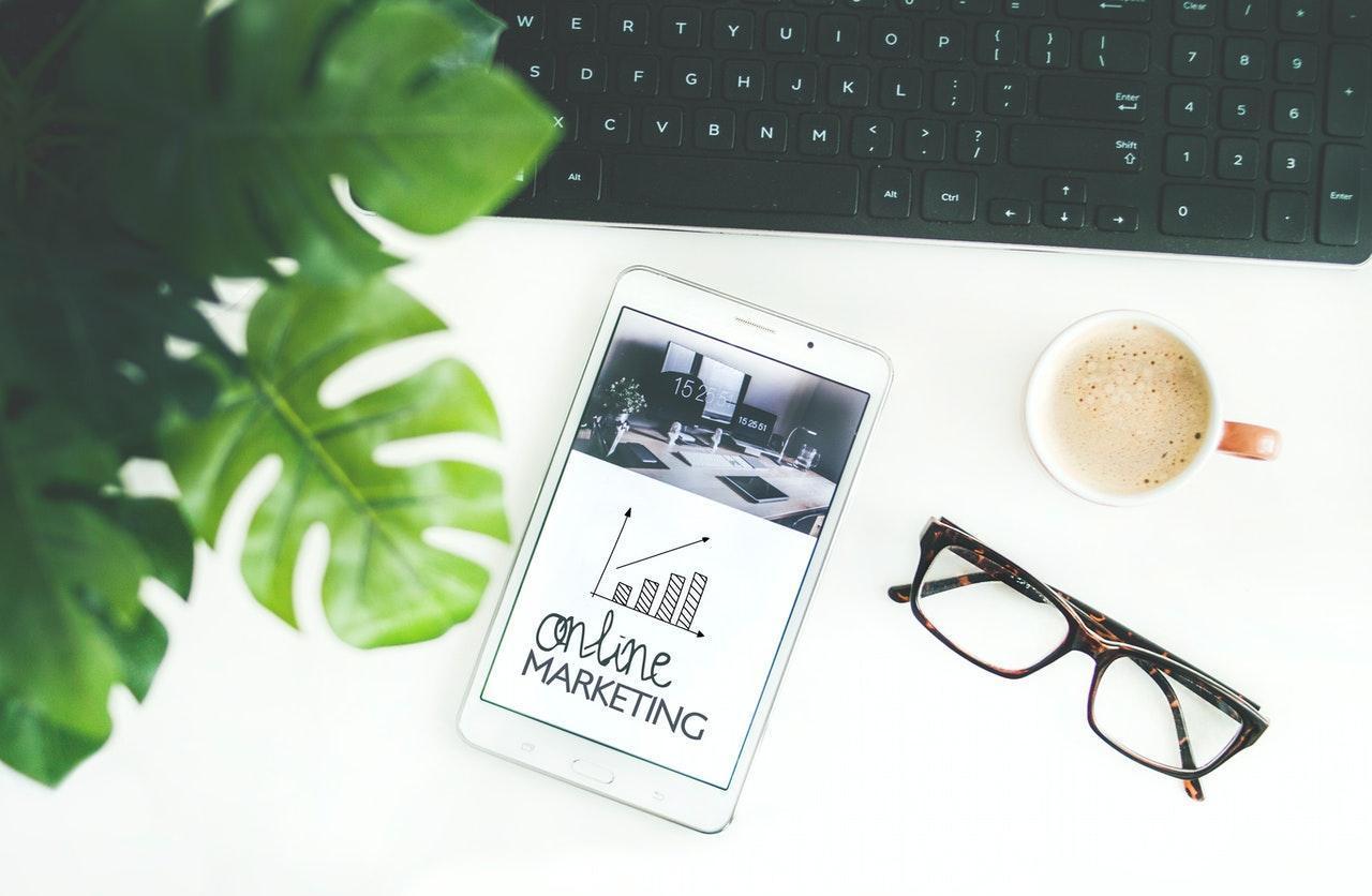 Des lunetes, un smartphone, une plante, un clavier sur une table blanche