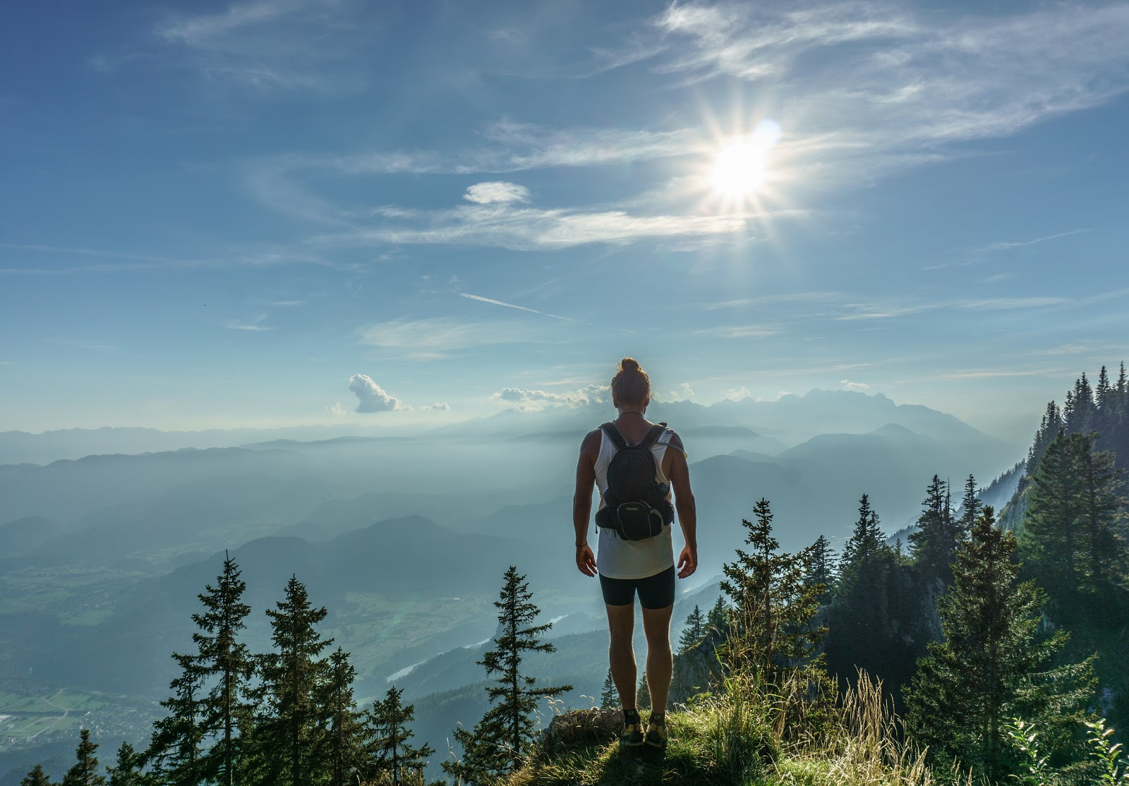 Man stands at top of BC Interior mountains while on RV vacation