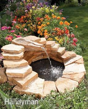 stacked stones creating an fountain in a flower garden