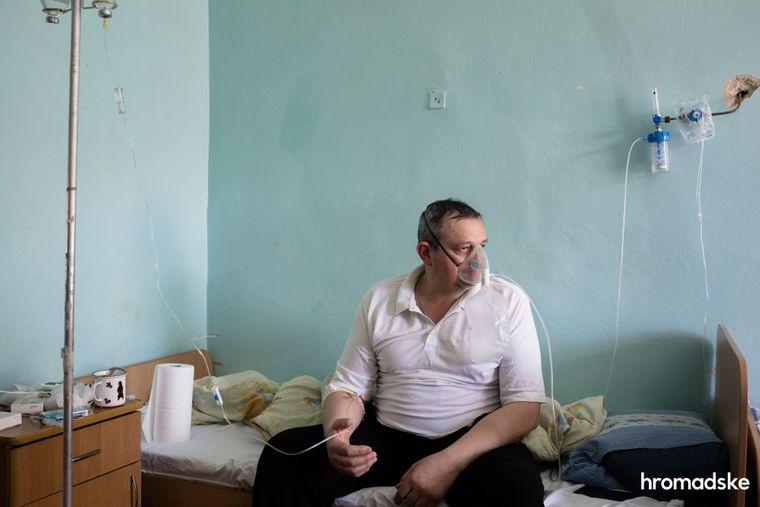 Мужчина, больной коронавирусом, сидит на кровати в инфекционном отделении больницы в городе Яремче Ивано-Франковской области