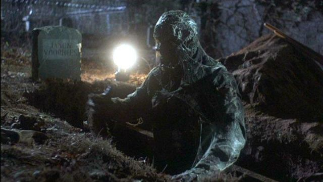 Still from Friday the 13th Pt 6 (1986). In a dark cemetery, a corpse covered in cobwebs emerges from an open grave.