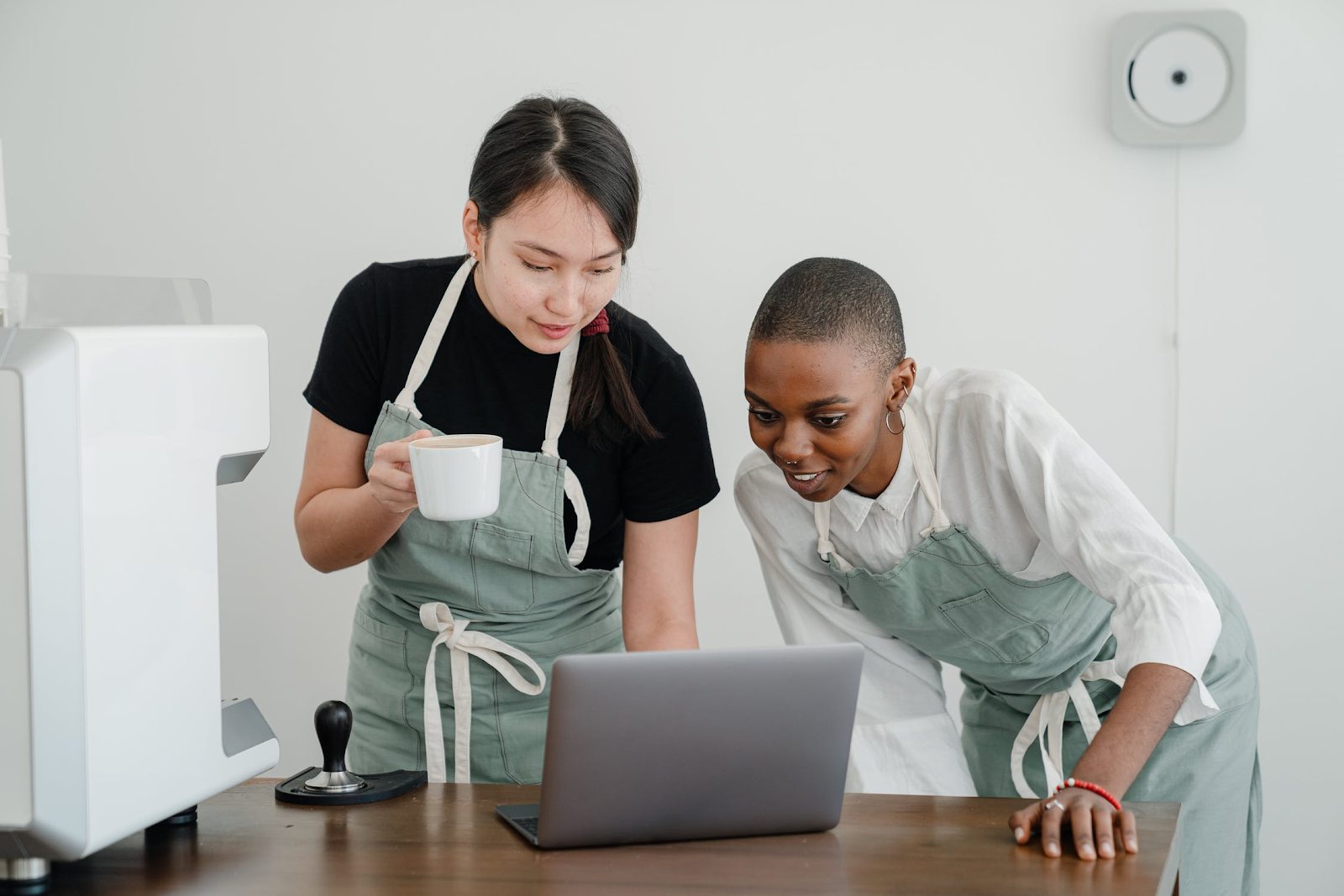 two women, one with a coffee cup, looking at a laptop screen
