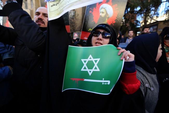 Участница акции протеста в Иране перед зданием посольства Саудовской Аравии с плакатом. Фото AFP/Scanpiх