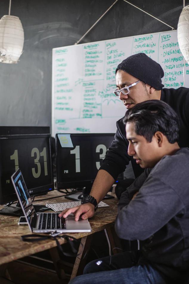 Diverse men coding on computer