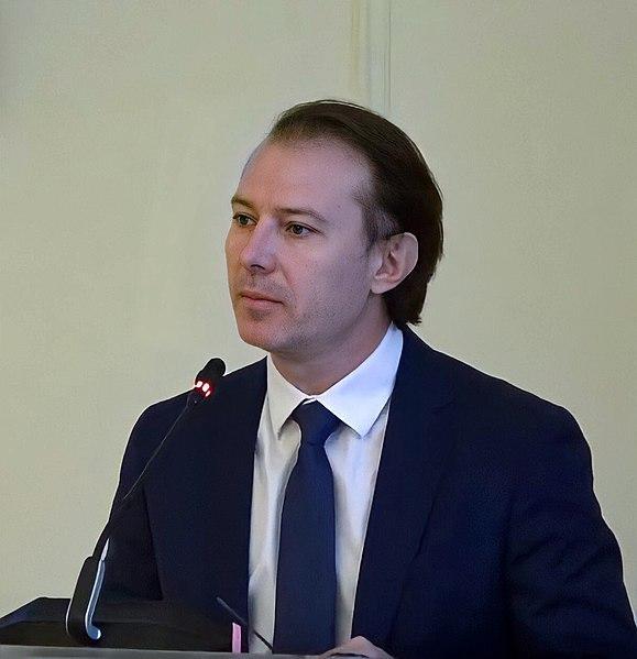 Un hombre con traje y corbata  Descripción generada automáticamente