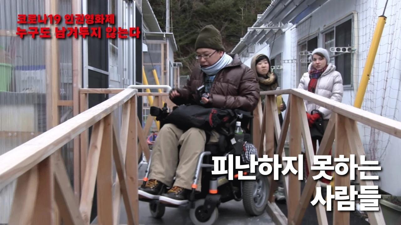 사진1. 영화 피난하지 못하는 사람들의 스틸컷. 좁은 통로 사이에 휠체어를 탄 사람이 있고 그 뒤로 두 명의 사람이 어딘가를 쳐다보고 있다.