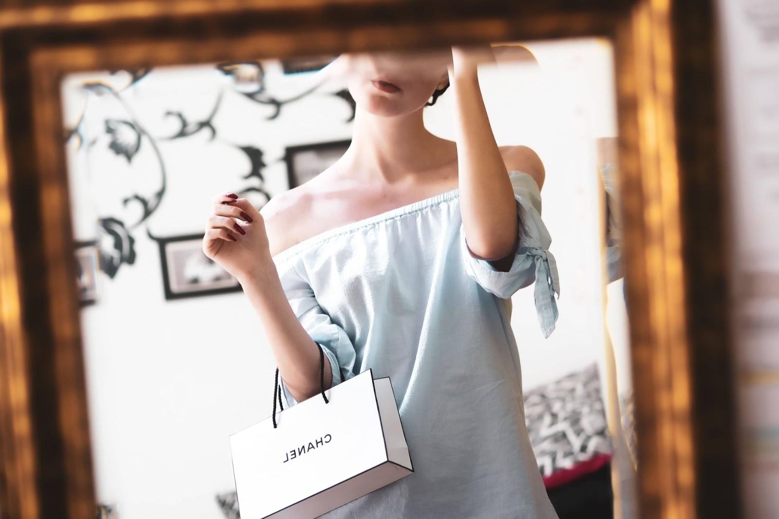 donna-che-si-specchia-confezione-chanel-sul-braccio
