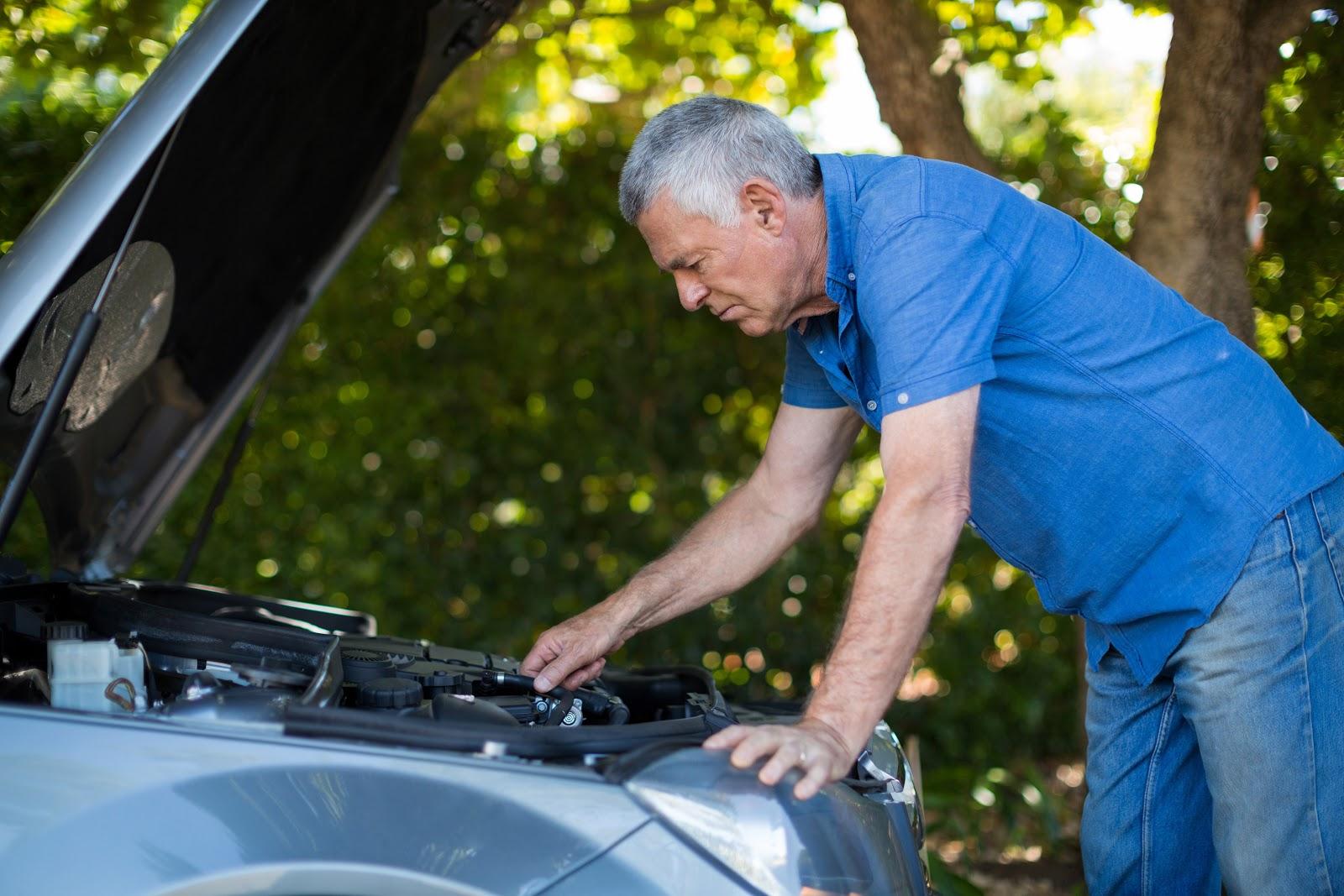 Um senhor está mexendo nas peças de seu carro.